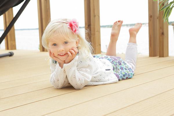 Tyttö makaa Twinson-terassilla, jonka paloluokka on lattiamateriaalien joukossa erinomainen.