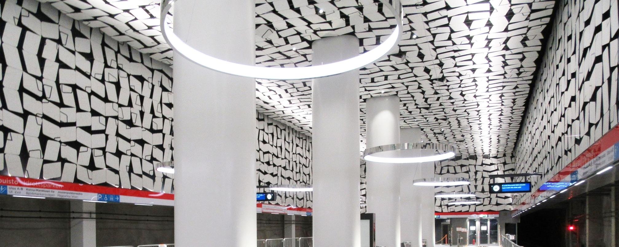 Muotoon leikattuja ja digitaalisella printatulla kuvalla päällystetyt sisäverhouslevyt metroasemalla.